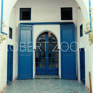 A blue arabic door in Marakech, Morocco.It consists of 2 big wings and many glass panels, inserted in a thick white wall.