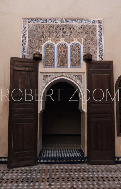 An arabic style door with tiles on the wall surrounding it