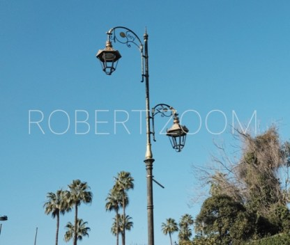 A street lamp in Marrakesh, Morocco, surrounded by trees and under a blue sky