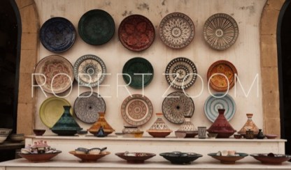 A display of several ceramic tajines and plates in different colors and sizes.