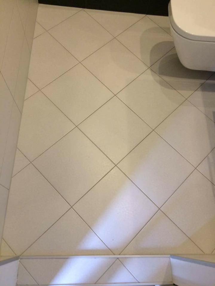 Łazienka zczerwonym dekorem ipółkami zpłytek