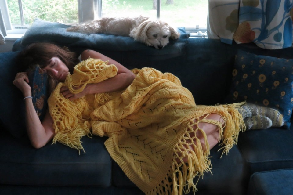 Sick with a cold, Robin Botie of Ithaca, New York, cuddles up with handknit afghan and dog.