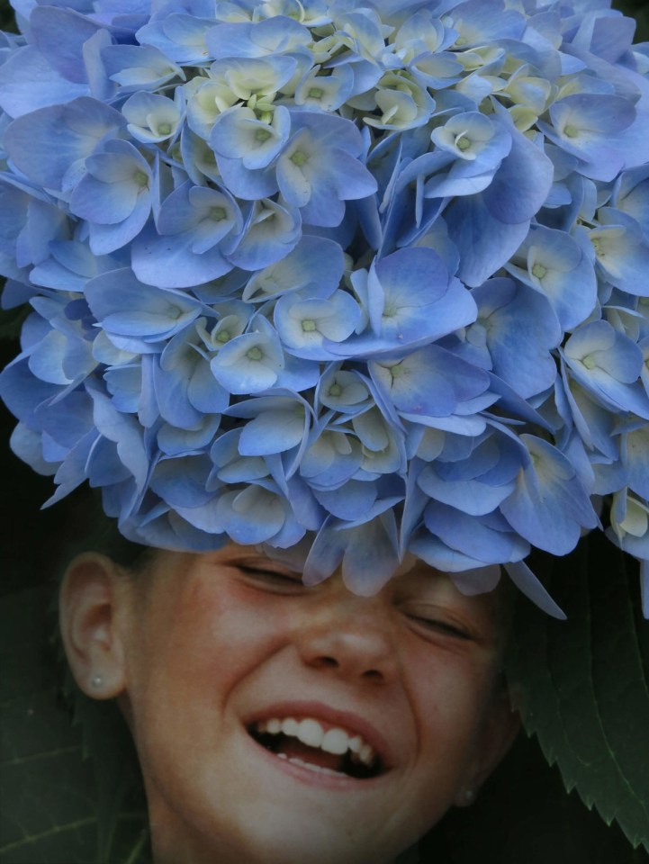 Robin Botie of Ithaca, New York, photographs a rhododendron and then Photoshops it over the face of her laughing daughter.
