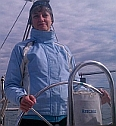 Robin G Coles in a blue sailing jacket at the helm of a Catalina Sailboat in Winthrop, MA Harbor