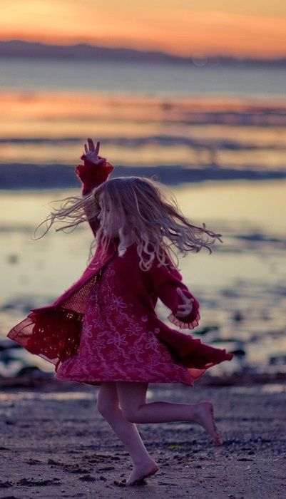 little girl spinning on the beach