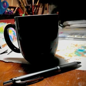 coffee cup and pen on a table