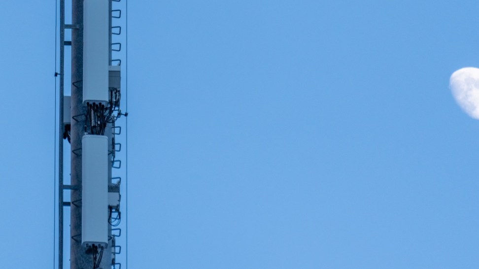 The moon rises behind an LTE tower.