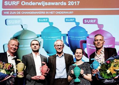 Ontvangers van de Surfnet Awards op het podium met de 3D-geprinte trofeeën in de hand. Op de achterwand geprojecteerd: een uitvergrootte afbeelding van de vier trofeeën.
