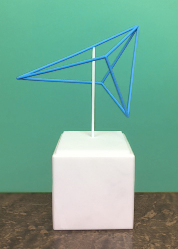 Een 3D-geprinte Zentih-award: het logo van Zenith in het blauw als ruimtelijk draadmodel op een wit-marmeren kubusvormig blokje.