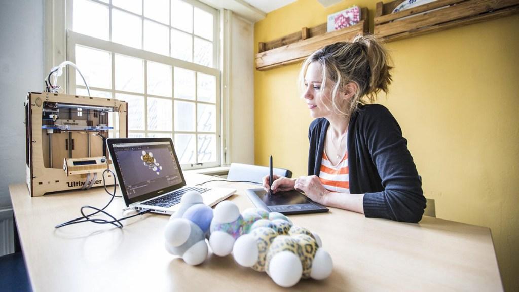 Foto van de 3D-printer en Katelijne aan het werk. In de voorgrond een 3D-print van een uitvergroot molecuul-model.