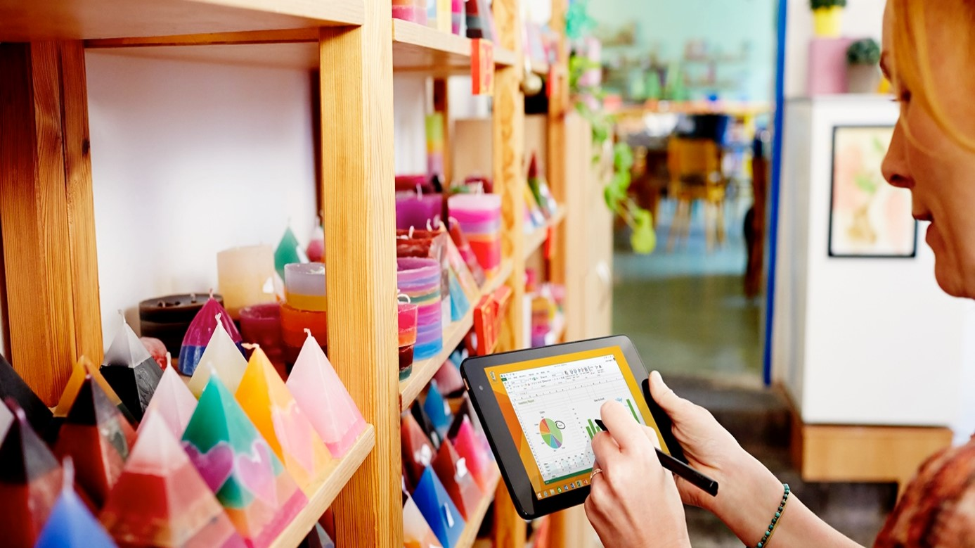 Woman holding a tablet taking stock of shop goods