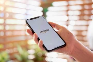 Hand met iPhone die Amazon logo toont