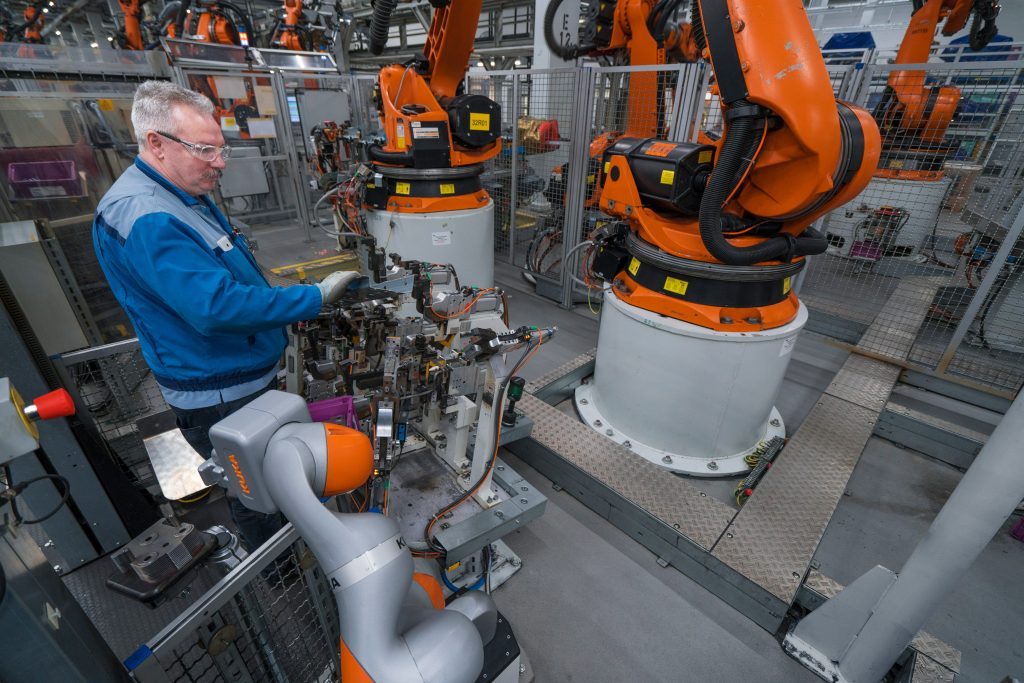 bmw worker in workshop with robots