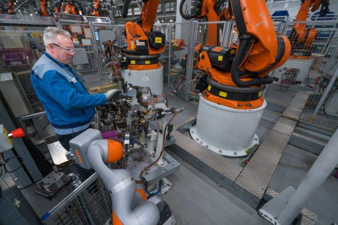 bmw worker in workshop with robots