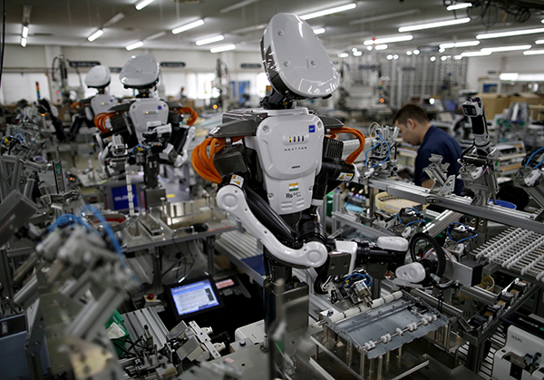FILE PHOTO: Humanoid robots work side by side with employees in the assembly line at a factory of Glory Ltd., a manufacturer of automatic change dispensers, in Kazo, north of Tokyo