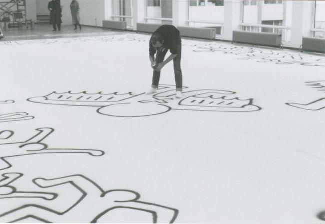 Keith Haring aan het werk in het Stedelijk Museum Amsterdam, waar hij in sneltreinvaart een groot doek vol spuit met figuurtjes (foto Chris Reinewald)