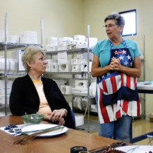 Jackie Graham explains how to pine-needle weave on pottery bowls to Sandy Holt in a recent class.