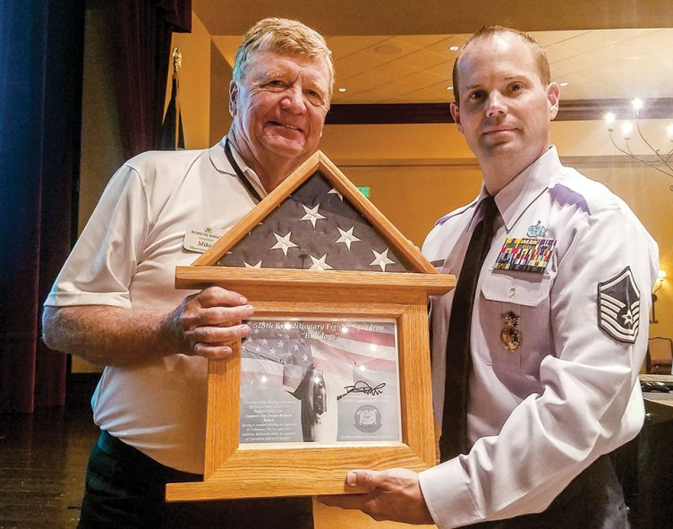 Sargent Robert Kent presents an American flag to Mike Hoernemann.