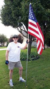 Quinn Sowell installing a flag for a Robson Ranch patriot.