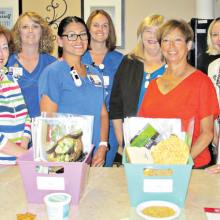 WLN members Tina Hoffenberg, Carolyn Thomas and Ana Corey meet with staff at Presbyterian Hospital's Diabetes Chronic Care Management Program. Displayed are some of the care boxes given to patients.