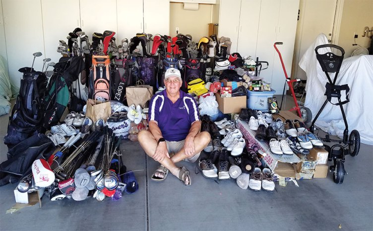 Russ sitting with all the donated golf equipment