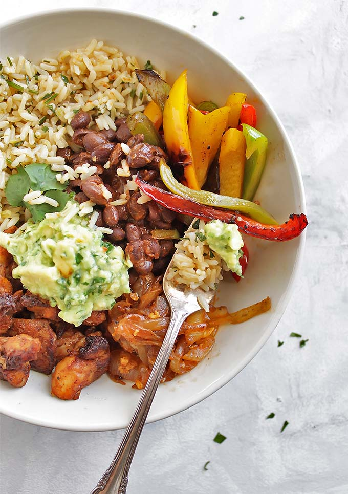 Chicken Fajita Bowls with Cilantro Lime Rice - Bowls with all of the best fajita ingredients: chicken, black beans, sauteed peppers and onions and guacamole! This recipe is HEALTHY and delicious. Gluten Free/Dairy Free | robustrecipes.com