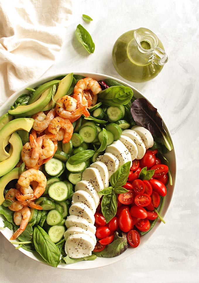 Loaded Caprese Salad with Shrimp - packed with all of the caprese classics plus some extra veggies. The salad is topped with a yummy basil dressing. This recipe only takes 25 minutes to make and is perfect for a quick dinner! Gluten free | robustrecipes.com
