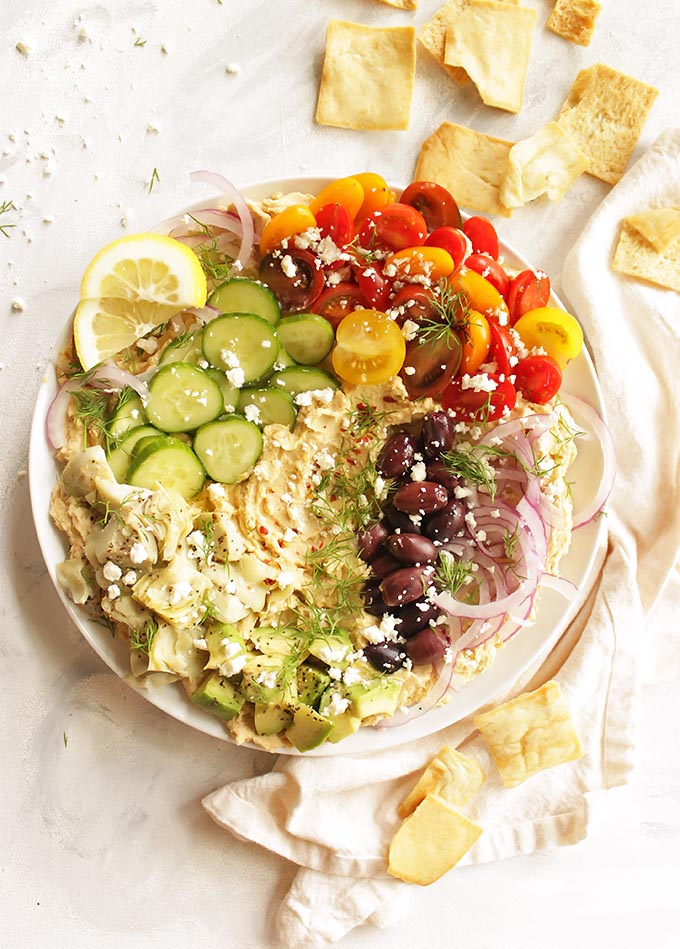 Creamy hummus topped with all the Greek fixings, artichoke hearts, tomatoes, cucumbers, red onion, kalamata olives, feta cheese, avocado, and fresh dill. It's served with sturdy pita chips or gluten free crackers for the ultimate dipping experience. Loaded Greek hummus only takes 20 minutes to make! The perfect appetizer for any party. (Gluten Free & Vegetarian) | robustrecipes.com