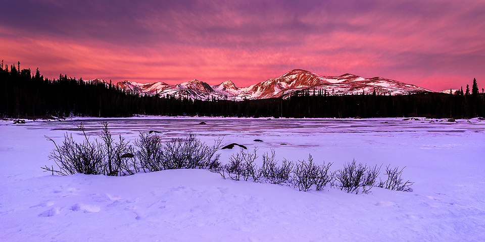 frozen lake with mountains and sunset