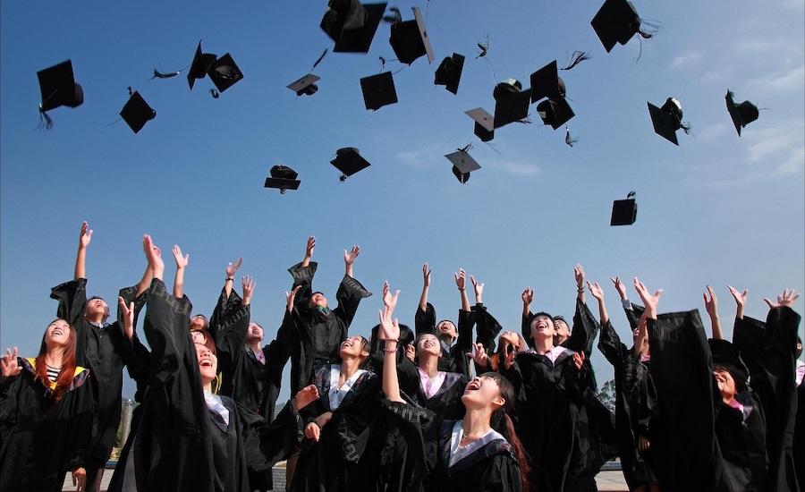 college grads toss hats in air