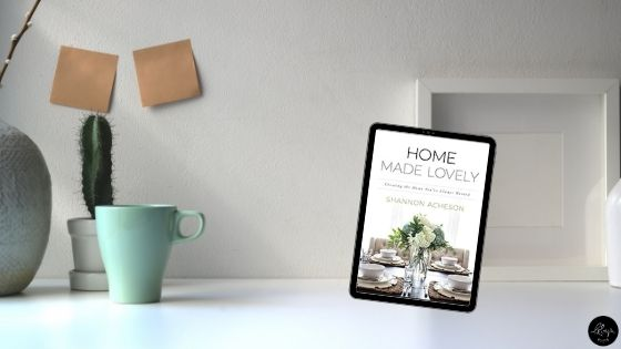 Image is a styled, minimalist photograph of a white table with a teal coffee cup, a small cactus, and a white picture frame on it. Overlaid is an image of the book cover for Home Made Lovely by Shannon Acheson.