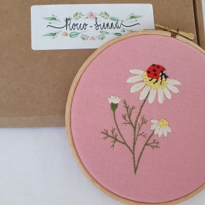 Ladybird and daisies on pink cotton embroidery