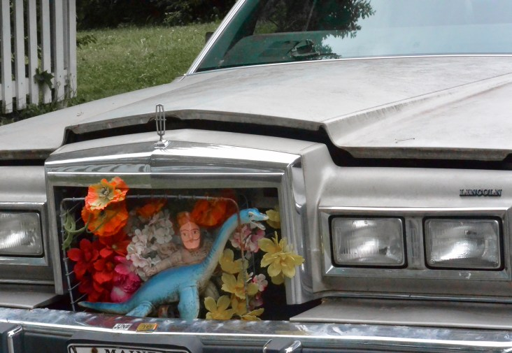 A strange shrine in the grill of a car.