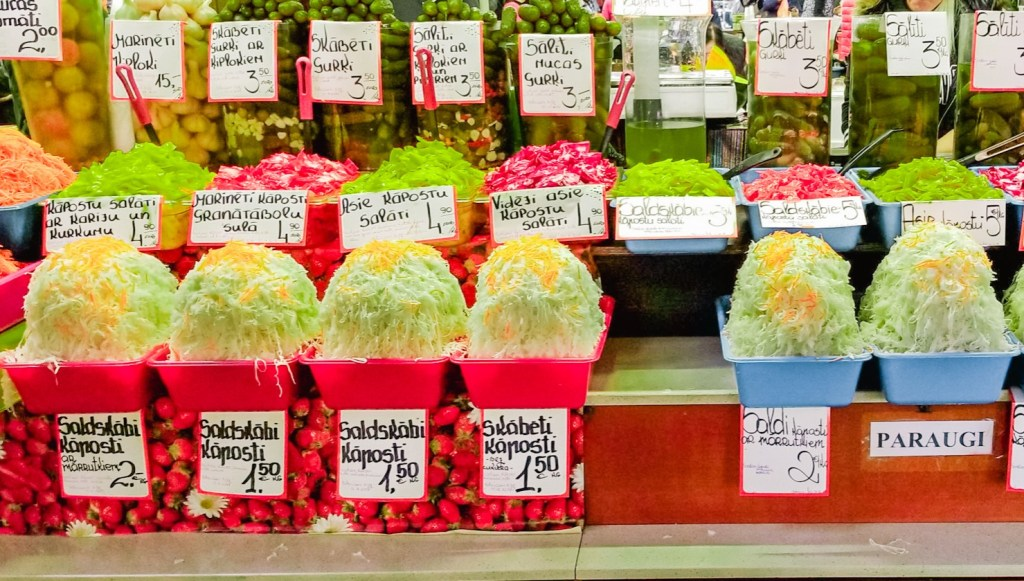 Red buckets filled with pickled cabbage on a table at Riga Central Market in Latvia