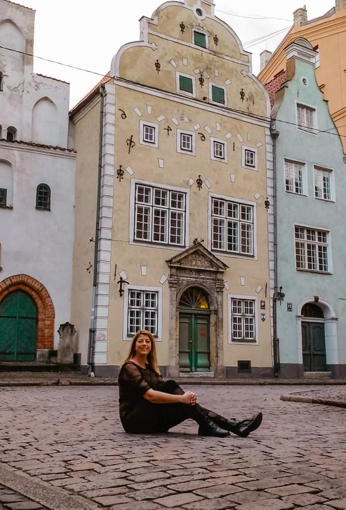 Eden Fite sitting in front of Three Brothers in Riga, Latvia
