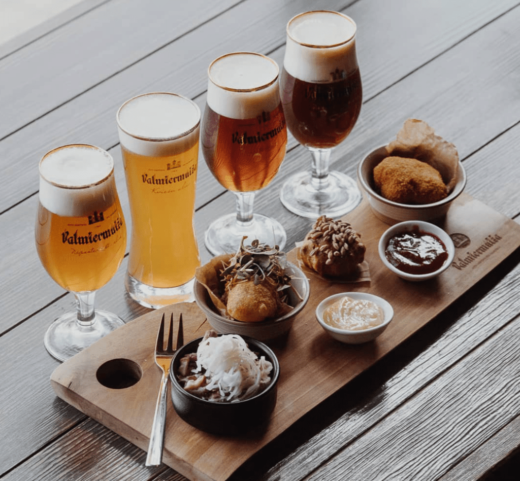 A line of four beers of different colors paired with small side dishes on a wooden cutting board