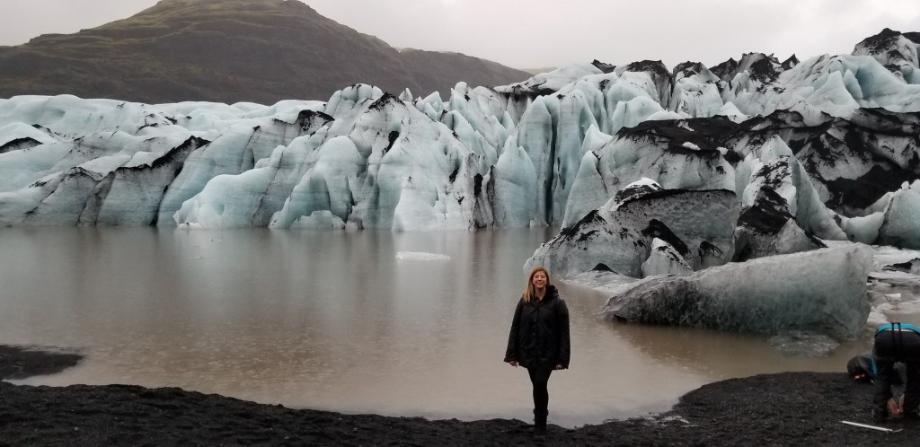 Eden Fite from Rock a Little Travel standing in front of a glacier in Iceland