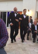 Two grooms coming down the aisle