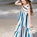 Girl on a sunny day at the beach in blue stripe cotton maxi dress and light grey floppy hat with tulle bow, kids outfit