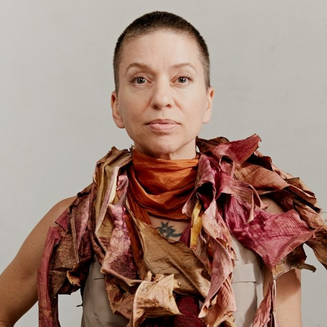 Ani DiFranco stands with her neck draped in a scarf made of tattered material of orange, reds, and browns