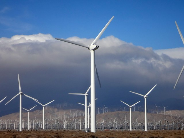 Field of wind turbines with blue sky and clouds