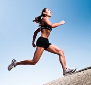 An elite athlete at peak action, running up a steep trail in the mountains.