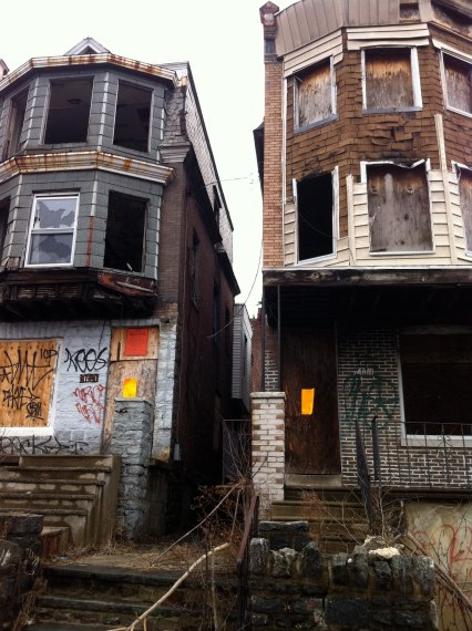 Abandoned houses at 4817 and 4815 Greene St directly next to the vacant lot, covered in graffiti in 2009.