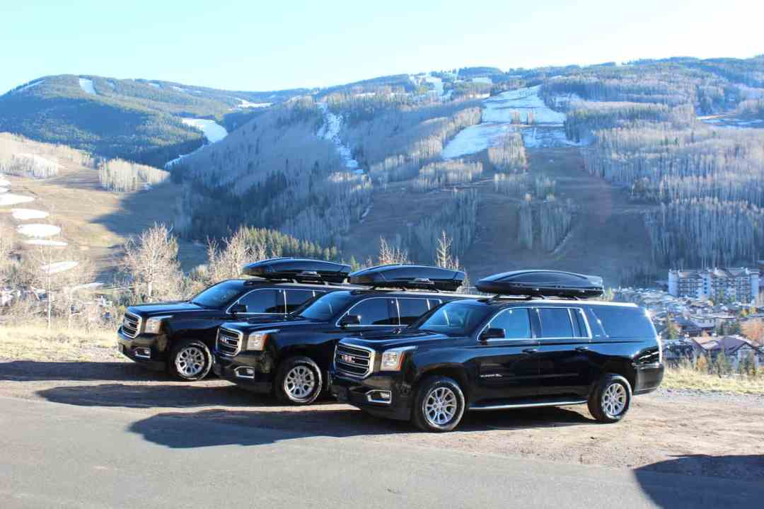 three black cars lined up in the mountains