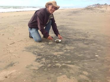 Manuel recolectando arena negra de la playa