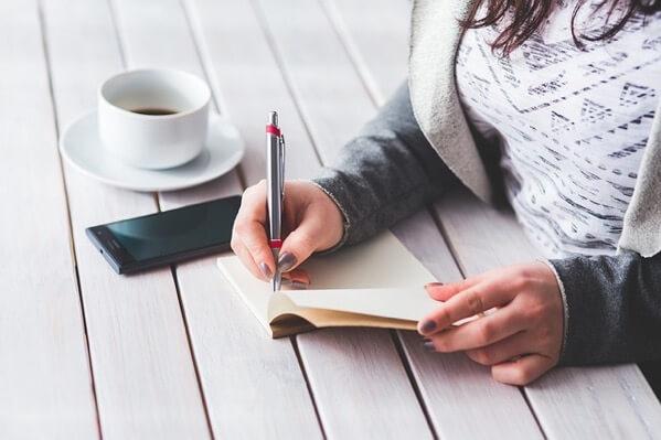 ノートにメモをしている女性