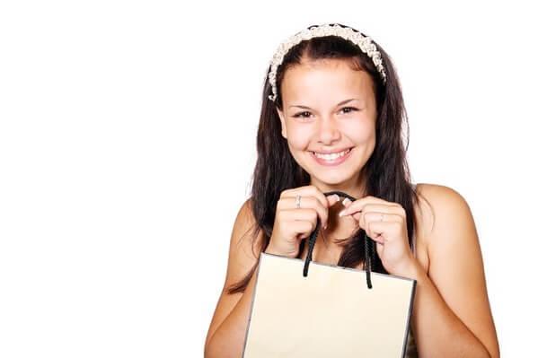 女性が買い物袋を笑顔で持っている