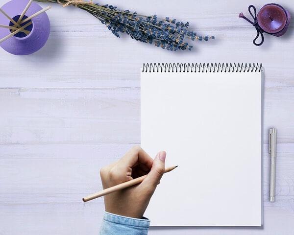 ノートに物を書いている女性