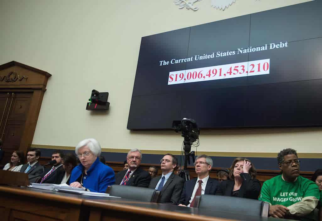 A screen shows the US national debt before US Federal Reserve chair Janet Yellen (front L) testifies before the House Financial Services Committee on Capitol Hill in Washington, DC, on February 10, 2016. Federal Reserve Chair Janet Yellen warned Wednesday that the US economy faced risks from tightening domestic financial conditions as well as global economic turmoil. / AFP / NICHOLAS KAMM (Photo credit should read NICHOLAS KAMM/AFP/Getty Images)