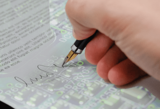 A hand writing some text on a document with a integrated circuit behind